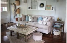 Love the comfortable yet still well done feeling in this room. Especially the floating shelf above the sofa and the baskets hung on the wall for throws.