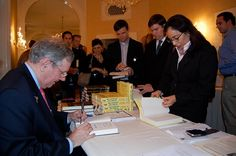 Steve Forbes signs a copy of his book Power Ambition Glory
