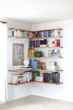 Simple shelving- brackets blend in to wall color to give a floating shelf look. Creative placement and color coordination.