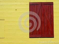 Bright yellow barn wall with red door.