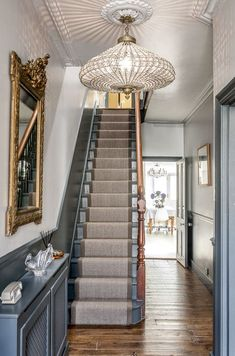 The large gold guilt mirror is a perfect accent to the grey walls and staircase., decor stairway The large gold guilt mirror is a perfect accent to the grey walls and staircase. Style At Home, Edwardian Haus, Victorian Hallway, 1930s Hallway, Edwardian Staircase, Stairway Lighting, Lights For Hallway, Lights On Stairs, Basement Lighting