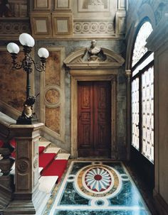 Venice: The second-floor landing of the grand staircase inside the Palazzo Papadopoli. The lamp, designed by Michelangelo Guggenheim, bears the Papadopoli family crest.