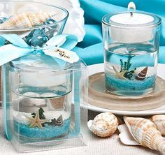 These Beach Candles will bring the calm of the ocean to your beach theme wedding or special event. Candle features a clear glass outer holder with a floating seascape design, topped with a central clear plastic holder with a white tea light candle inside. Shells, a starfish and a sea shrub are resting in a floor of vibrant blue pebbles and are suspended in a clear gel to ensure their stability.