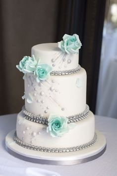 White cake with mint green roses and bling