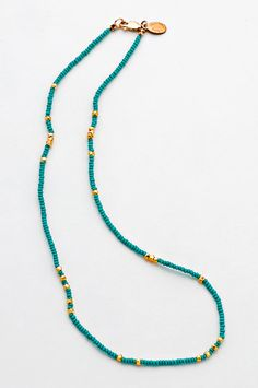 This necklace features 16 inches of turquoise seed beads strung on silk and accented with small gold vermeil bits. Fastens with a gold filled