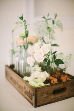 a cluster of flower vases in an old soda crate wedding centerpiece