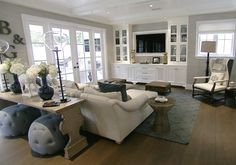 Great living room set-up.  Built-ins, french doors, nice  bright, sofa table with stools for extra seating....