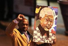A well-wisher carries a portrait of former South African President Nelson Mandela outside the Pretoria hospital where former President Mandela is being treated, June 26, 2013. REUTERS-Siphiwe Sibeko