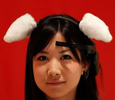 The Teleglaph Hanako Miyake demonstrates Japanese research project team Nerowears Necomimi at its promotional event in Tokyo. The strap-on cat ears can wiggle, twitch, perk up or flop down by responding to users brainwaves...