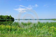 Calm surface of lake Kis-Balaton surrounded with lush vegetation in bright summer day, Heviz, Hungary.