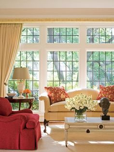 A Chippendale-style camelback sofa is salvaged and reupholstered by designer Julio Quinones, who also added rosette-like custom pleating at the corners for a delicate, personal touch - Traditional Home®