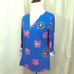 Lilly Pulitzer top in Of Coursage EUC Lilly Pulitzer cotton long sleeve top in Of Corsage print. Button tab sleeves can be worn up or down. Gold LP buttons. Color is slightly faded around collar as shown in the third picture, and also near hem. This top still has a lot of life to it. No holes or stains. 100% Pima cotton. trades LP runs smaller than some women's brands. I'm happy to provide measurements. I don't smoke but love my rescue cat. Lilly Pulitzer Tops Blouses