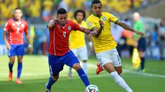 Mauricio Isla of Chile and Luiz Gustavo of Brazil compete for the ball