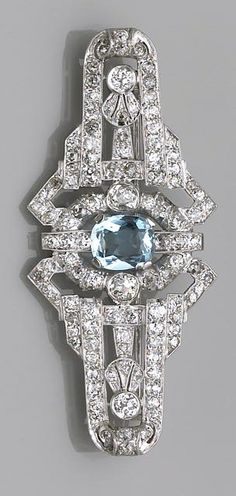 An aquamarine and diamond brooch, circa 1950 centering an oval-shaped aquamarine within a surround of old European-cut diamonds; aquamarine weighing approximately: 2.10 carats; estimated total diamond weight: 4.20 carats; mounted in platinum; length: 2 11/16in.