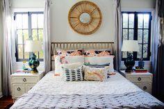 Beautiful, eclectic bedroom with rattan mirror