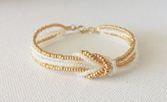 Beautiful love knot bracelet made with gold and white pearl seed beads. These bracelets are made with a pretty sturdy filament, so they are not floppy. Seed Bead Jewelry, Wire Jewelry, Jewelry Crafts, Beaded Jewelry, Jewelery, Handmade Jewelry, Square Knot Bracelets, Bead Loom Bracelets, Bridesmaid Bracelet