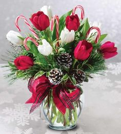 Send holiday cheer and tasty  treats too with this vase of red  and white tulips, pinecones  and candy canes.