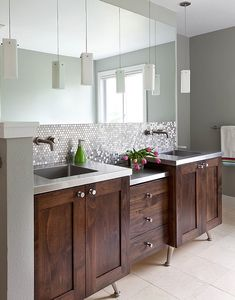 Done in varying tones of silver to match the vanity countertop, penny-round tiles add subtle sparkle to this bathroom.