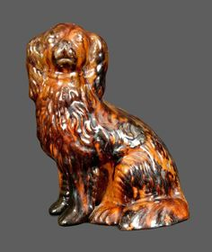"""Lot Passed Extremely Rare Lead and Manganese Glazed Redware Figure of a Spaniel, Stamped """"SOLOMON BELL / Strasburg, Va"""" and Incised in Script """"Solomon Bell,"""" third quarter 19th century, molded figure of a seated spaniel the surface decorated with streaks of manganese and covered in a heavy lead glaze over a mottled orange and olive ground. Underside impressed with an early two-line maker's mark of Shenandoah Valley master potter, Solomon Bell, which reads """"SOLOMON BELL / Strasburg, Va.""""…"""