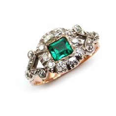Emerald and diamond cluster ring, set in silver and gold with a fluted gold shank.  English c1800. S.J. Phillips.