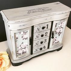 This vintage jewelry box has been painted gray and black, lightly distressed and sealed with a soft wax. The doors and drawer sides have been decoupaged with a vintage rose print. The top opens to a large mirror with storage compartments. There are two doors that open to necklace carousels and a ring pillow. There are four drawers down the center. Interior is a soft gray velveteen. Measurements: approx 10 3/4H x 13 1/2W x 5D These are vintage pieces, so they are not in perfect con...