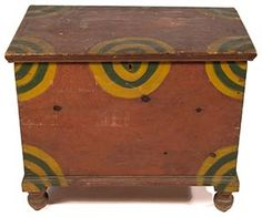 """This brightly paint-decorated pine blanket chest is from Pennsylvania, circa 1830. The chest is a convenient diminutive size at 25"""" x 30¾"""" x 18¾"""". The case is dovetailed, with molding applied to the lid and at the base. The piece is raised on turned acorn-form feet. The surface features the original dry green and yellow paint on a salmon ground. The chest is in overall excellent condition, with some warping to the lid. The winning bidder took this chest home for $7450 (est. $2000/3000)."""