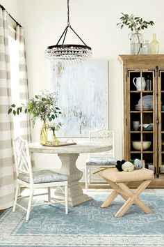Sophisticated dining room with round table, crystal chandelier, marbleized fabric, and raffia x-bench