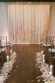 Rose petals and candles line this aisle and lead to the a pink pastel ribbon backdrop: http://www.stylemepretty.com/texas-weddings/dallas/2014/12/10/understated-elegance-in-dallas-texas-at-brookhollow-golf-club/ | Photography: Nicole Berrett - http://www.berrettphotography.com/