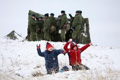March 15, 2012 Children play with snowballs after arriving to watch a drill, conducted by Russian airborne troops, at a firing ground near the settlement of Sadovyi, Russia. Eduard Korniyenko/Reuters