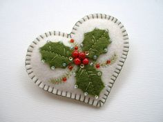 Hi!    This holiday heart pin, is made of 100% wool felt, and it measures just over 2 1\/2 across. Onto creamy off white felt, Ive add a few holly leaves, and red, bead berries. Touches of embroidery and clear beads accent the leaves, and a few fir sprigs peek out from between the holly.  The edge of this pin is blanket stitched for a nice finished look, and its been made so it will keep its shape and not bend when your wearing it. ;)    I create all of my things in my smoke free home…