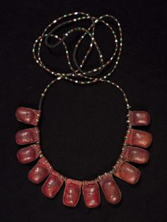 """Prayer necklace Fulani, Nigeria Red leather, brass rings, cord, small colored crimp beads, prayers Amulets average 1"""" (2.5 cm) by 5/8"""" (1.5 cm), cord is 52"""" (132 cm) long Early to mid 20th century"""