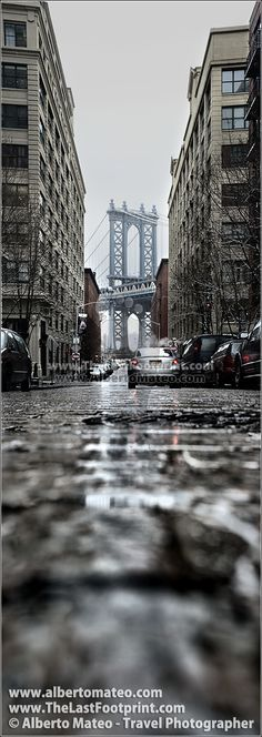 Manhattan Bridge from Dumbo streets, in Brooklyn, New York. The pillar of the Bridge is so impressive... I tried to relate it with the street around... and the rain gave some ambient to the image... | By Alberto Mateo, Travel Photographer.