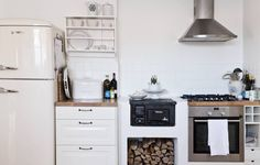 Anne-Mari ja Olof ovat erittäin tyytyväisiä kaasuhellaan, uuni on sähkö-käyttöinen. Musta, pieni puuhella on ostettu vanhana, ja se asennettiin remontin yhteydessä. Vasemmalla seinällä oleva astiahylly on Olofin tekemä. Jääkaappi ja liesituuletin ovat Gorenjen.