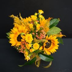 Beautiful yellow sunflowers and spray roses make this arrangement sunny and bright! Accented with stock, solidaster and lemon leaf, this arrangement is certainly cheery.