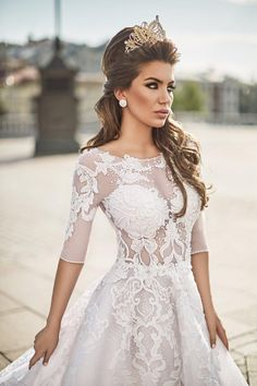 Vestido de noiva imperial em tule branco com aplicação de rendas em arabescos. A saia tem camadas de tule com renda aplicada e é armada com crinol, que aumenta o volume e cria este efeito glamouroso.
