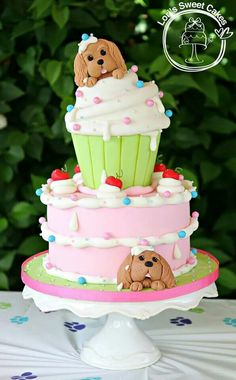 Andrea's signature cupcake style two tier cake customised with two puppies. Would also look cute with kittens! Cake by Lori's Sweet Cakes.
