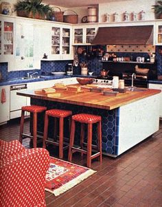 September 1980. A brick floor and glazed tiles on walls give a special shine to the kitchen. To make mealtimes easy, the work island contains drawers, storage bins, open shelves and a sink.