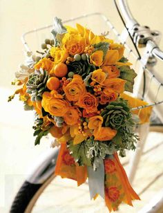 bright yellow ranunculus, gold roses, perfumed freesia, ilex berries, and clementines form the warm foundation, while dusty-miller leaves, b...