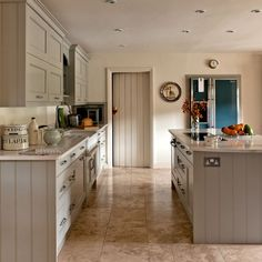 This fabulous country kitchen oozes muted gorgeousness. We can't get enough of the Shaker style cabinets by Cotteswood and the Mandarin Stone travertine floor tiles. Lovely.