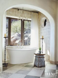 Designed by Jana Parker Lee, the master bath of this Arizona home has a modern tub made rustic by tile details.