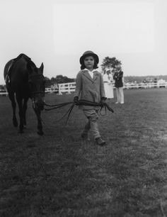 August 1934: Jacqueline Bouvier leading her pony, 'Buddy,' at the Southampton Riding and Hunt Club for the annual horse show, Long Island, New York