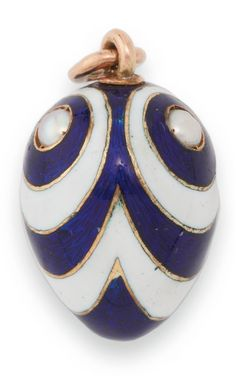 *A FABERGÉ GEM-SET GOLD AND GUILLOCHÉ ENAMEL EASTER EGG PENDANT, WORKMASTER AUGUST HOLLMING, ST. PETERSBURG, 1898-1908 mounted with three seed pearls, each surrounded by rings of alternating cobalt blue over a guilloché ground and opaque white enamel emanating from the pearls, struck with workmaster's initials, 56 standard height 7/8 in. (2.2 cm)