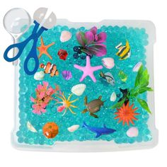 Our fun sensory Ocean Exploration Discovery Box and sensory bin will introduce kids to a magical world of miniature sea creatures, sparkling gems and crystals, and colorful shells and ocean plants. Ki
