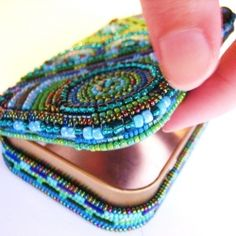 An altoids tin heavily embellished with glass seed beads.