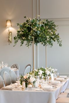 Fresh and organic, this tall centerpiece topped with lush greenery is a showstopper! Photo Credit: Mango Studios   Planner: RDT Events + Beauty   Florals: Fleuristic Garden & Flower Studio