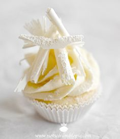 White Christmas Cupcakes topped with White Chocolate Cream Cheese Frosting  White Chocolate Curls #christmas #cupcakes #recipes http://thecupcakedailyblog.com/white-christmas-cupcakes/