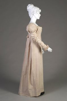 Cotton day dress, ca. 1808-1812. White cotton day dress printed with red and blue floral rondels overall. The dress with scoop neck and high waist. A panel from the waistband flaps up over the bust, ties at the waist are pulled to the tightly pleated back. The short sleeves with sewn in fitted undersleeve with ruffled wrist.