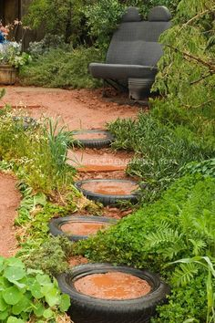 not sure what's wrong w/me, but i think this is super cool...Recycled garden with old car tires and car seat bench, wide view