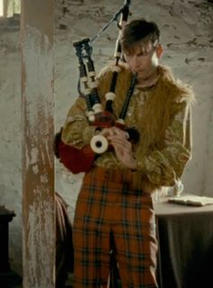 My life is complete: David Tennant wearing plaid bell bottoms, a paisley shirt, and a faux fur vest. And he's playing the bagpipes.
