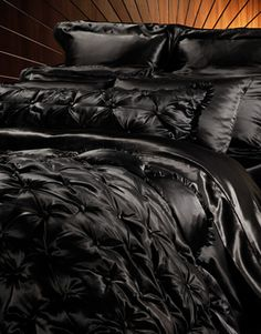 Home Collection - Glossy silk in black. Black bedspread with pink and black pillows and a few lacey ones.